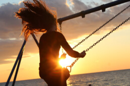Woman on a swing with sunset in background